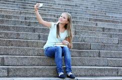 Muchacha bonita del adolescente que toma el selfie mientras que se sienta en las escaleras Imagenes de archivo