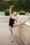 Muchacha bonita del ballet que la estira tendones de la corva Foto de archivo libre de regalías