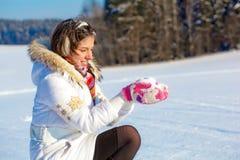 Muchacha bonita del estudiante con nieve en palmas Imagen de archivo