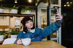 Muchacha bonita del inconformista que se sienta en un café y que presenta para la cámara de su teléfono Fotografía de archivo