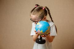 Muchacha bonita del niño con los vidrios en casa que sueña con viaje y a Imagenes de archivo