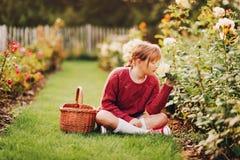 Muchacha bonita del niño que juega afuera en jardín de flores Foto de archivo