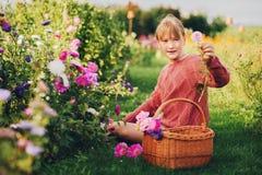 Muchacha bonita del niño que juega afuera en jardín de flores Foto de archivo libre de regalías