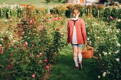 Muchacha bonita del niño que juega afuera en jardín de flores Fotos de archivo