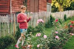 Muchacha bonita del niño que juega afuera en jardín de flores Fotografía de archivo