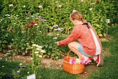 Muchacha bonita del niño que juega afuera en jardín de flores Imagen de archivo libre de regalías