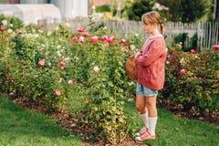 Muchacha bonita del niño que juega afuera en jardín de flores Imágenes de archivo libres de regalías