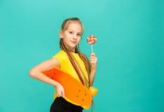 Muchacha bonita del patinador que sostiene el monopatín Foto de archivo libre de regalías