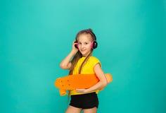 Muchacha bonita del patinador que sostiene el monopatín Imagenes de archivo