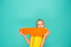 Muchacha bonita del patinador que sostiene el monopatín Imagen de archivo