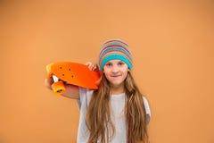 Muchacha bonita del patinador que sostiene el monopatín Fotografía de archivo