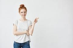 Muchacha bonita del pelirrojo con las pecas que sonríe señalando la derecha del finger en el fondo blanco Imagen de archivo libre de regalías