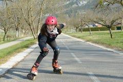 Muchacha bonita del preadolescente en pcteres de ruedas en casco en una pista Fotografía de archivo libre de regalías