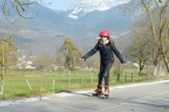 Muchacha bonita del preadolescente en pcteres de ruedas en casco en una pista Foto de archivo libre de regalías