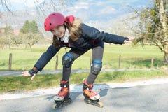 Muchacha bonita del preadolescente en pcteres de ruedas en casco en una pista Imagenes de archivo