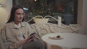 Muchacha bonita del retrato que manda un SMS en su teléfono celular que se sienta en la tabla en el restaurante El pedazo de tort metrajes