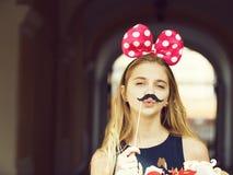 Muchacha bonita divertida con los oídos de ratón lindos y el bigote negro imagen de archivo libre de regalías