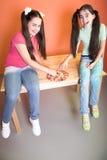 Muchacha bonita dos con la pizza en el escritorio Fotos de archivo