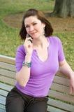Muchacha bonita en banco de parque que habla con el teléfono celular fotos de archivo