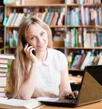 Muchacha bonita en biblioteca que mecanografía en el ordenador portátil y que habla en el teléfono Imagen de archivo libre de regalías