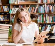 Muchacha bonita en biblioteca usando la tableta y el hablar en el teléfono Fotografía de archivo libre de regalías
