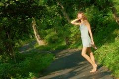 Muchacha bonita en el camino de bosque Foto de archivo