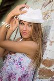 Muchacha bonita en el sombrero blanco del sombrero de ala al lado del ladrillo viejo Fotos de archivo libres de regalías