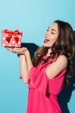 Muchacha bonita en el vestido que sostiene la caja de regalo en sus palmas Imagen de archivo libre de regalías
