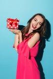 Muchacha bonita en el vestido que sostiene la caja de regalo en sus palmas Fotos de archivo