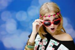 Muchacha bonita en gafas de sol en forma de corazón en azul Fotografía de archivo