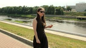 Muchacha bonita en gafas de sol en la calle que camina y que come el helado Leva constante almacen de video