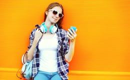 Muchacha bonita en gafas de sol y auriculares usando smartphone Imagenes de archivo