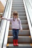 Muchacha bonita en gumboots rojos abajo en la escalera móvil Foto de archivo