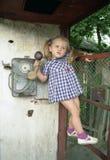 Muchacha bonita en la cabina de teléfono Foto de archivo libre de regalías