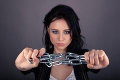 Muchacha bonita en la chaqueta de cuero con las cadenas en sus manos Imagen de archivo