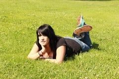 Muchacha bonita en la hierba en su mano del estómago en el Ch Fotografía de archivo