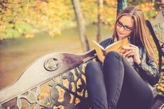 Muchacha bonita en la lectura de la caída Fotos de archivo libres de regalías