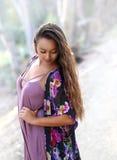 Muchacha bonita en la ropa colorida que mira abajo la tierra Foto de archivo