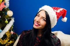 Muchacha bonita en la sonrisa feliz del sombrero de Papá Noel por otra parte Imagen de archivo libre de regalías