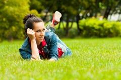 Muchacha bonita en los tejanos que mienten en una hierba Fotografía de archivo libre de regalías