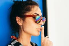 Muchacha bonita en muestra del silencio de la demostración de las gafas de sol Fotografía de archivo