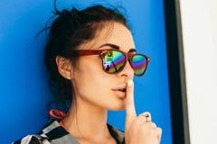 Muchacha bonita en muestra del silencio de la demostración de las gafas de sol Imagenes de archivo