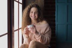 Muchacha bonita en un alféizar con la taza en sus manos Foto de archivo libre de regalías