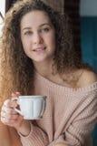 Muchacha bonita en un alféizar con la taza en sus manos Fotografía de archivo