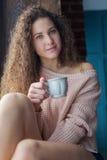 Muchacha bonita en un alféizar con la taza en sus manos Fotografía de archivo libre de regalías