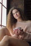 Muchacha bonita en un alféizar con la taza en sus manos Imagen de archivo