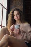 Muchacha bonita en un alféizar con la taza en sus manos Imagenes de archivo
