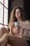Muchacha bonita en un alféizar con la taza en sus manos Fotos de archivo libres de regalías