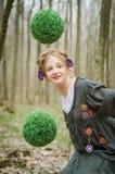 Muchacha bonita en un oscilación en el bosque con las bolas verdes decorativas Fotos de archivo
