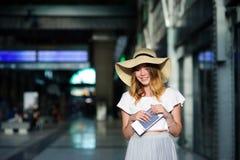 Muchacha bonita en un sombrero de ala ancha con el pasaporte y boletos en una mano Foto de archivo libre de regalías